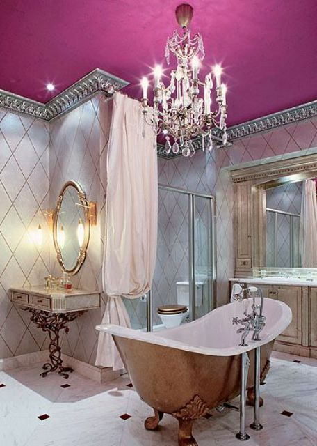 a vintage feminine bathroom with a pink ceiling and a lawfoot tub, a vintage crystal chandelier
