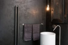 11 an industrial bathroom with a white free-standing sink that pops up