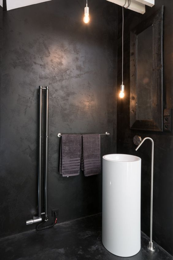 an industrial bathroom with a white free-standing sink that pops up