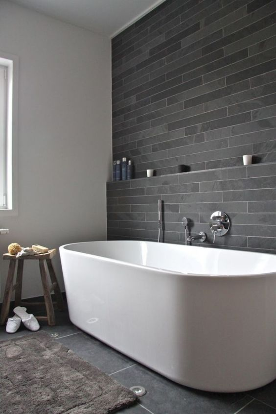peaceful grey tile bathroom with a large freestanding bathtub