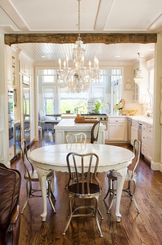 a rustic shabby chic kitchen with a sheer crystal chandelier on a white chain