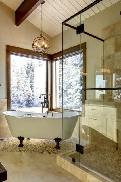 a white clawfoot bathtub with black legs next to the windows for a cool look