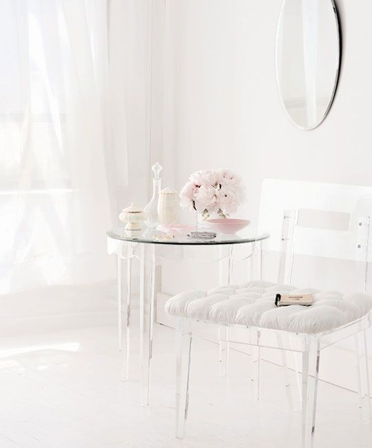 a lucite chair with a white upholstered seat and a table with lucite legs for a feeling of lightness