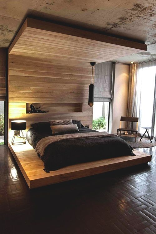 a sculptural black pendant lamp makes a statement in this masculine sleeping space