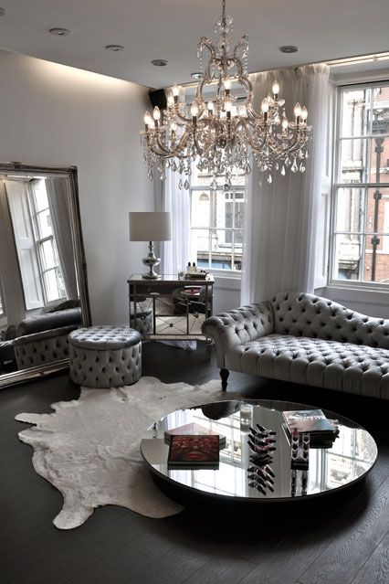 a silver grey living room with a large crystal chandelier with candle-inspired bulbs