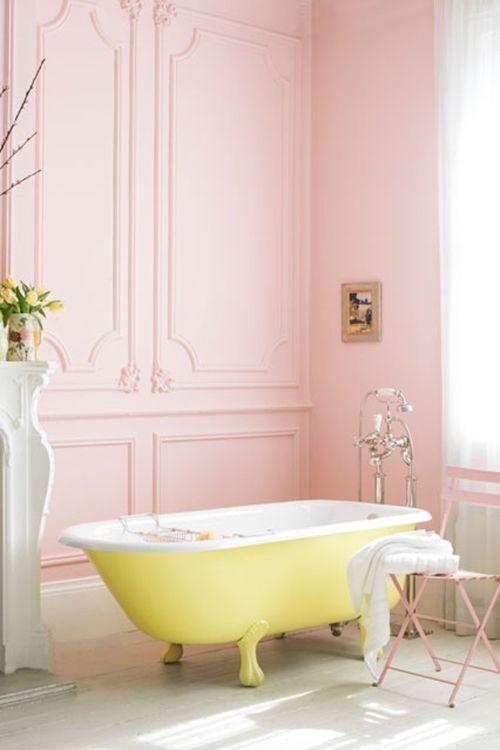 a fun sunny yellow clawfoot bathtub in a pink bathroom