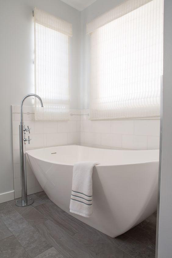 a neutral bathroom with a niche for a sculptural bathtub