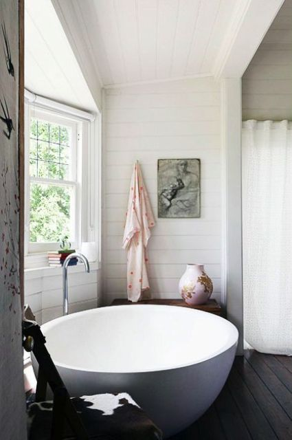 a large round bathtub next to the window for a view