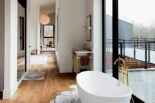 15 an oval freestanding bathtub next to the glazed wall on marble tiles