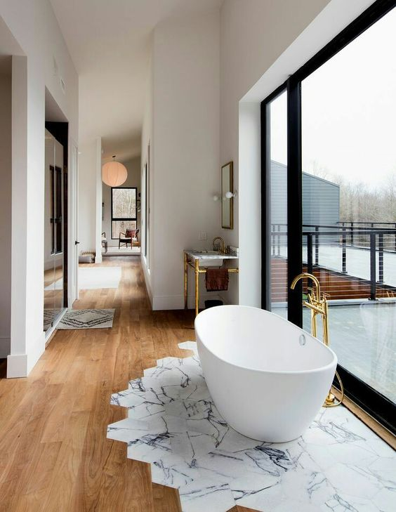 an oval freestanding bathtub next to the glazed wall on marble tiles