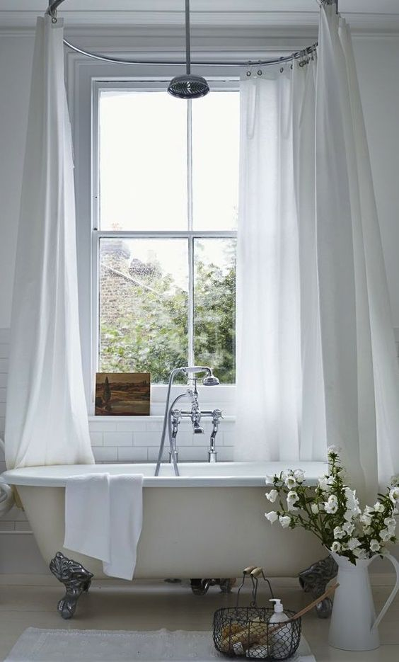 neutral bathroom with an ivory bathtub on metall legs and a shower over it