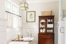 16 elegant vintage bathroom with a clawfoot tub, a wooden cabinet and a carpet