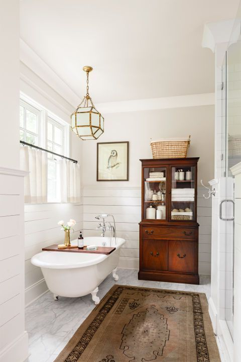 elegant vintage bathroom with a clawfoot tub, a wooden cabinet and a carpet