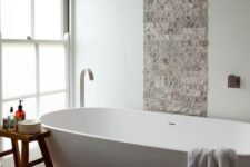 16 stone tiles and a wooden stool create a textural look and a large bathtub makes you relax