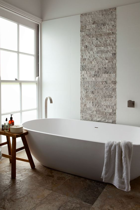 stone tiles and a wooden stool create a textural look and a large bathtub makes you relax