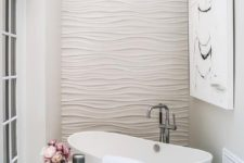 17 a glam bathroom with a textural wall and a small freestanding tub