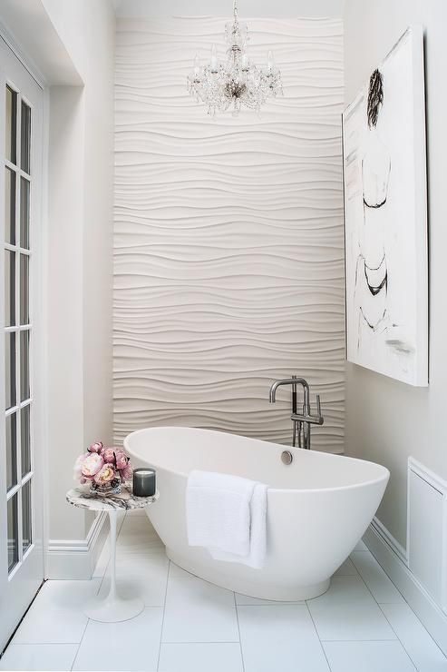 A Glam Bathroom With A Textural Wall And A Small Freestanding Tub