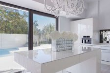 17 a minimalist white kitchen is spruced up with a modern crystal covered chandelier