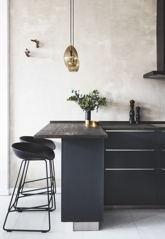 elegant black kitchen island with a wooden counter, small modern stools