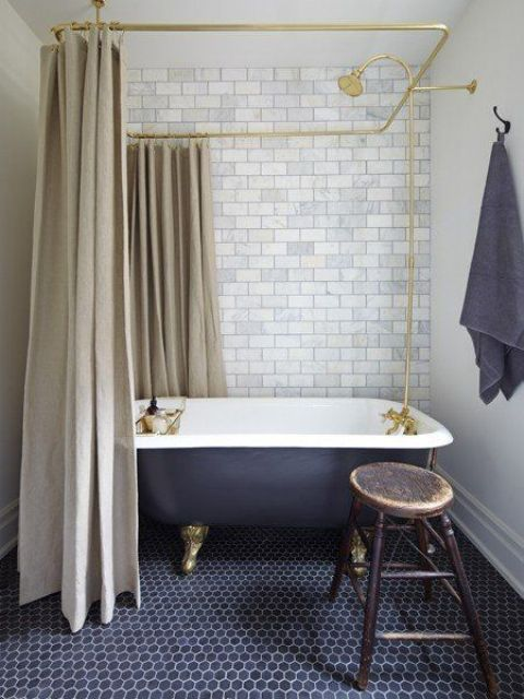 retro-inspired bathroom with a black clawfoot tub on metallic legs looks very elegant