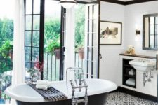 18 20s inspired bathroom in black and white with an oval black clawfoot tub on legs
