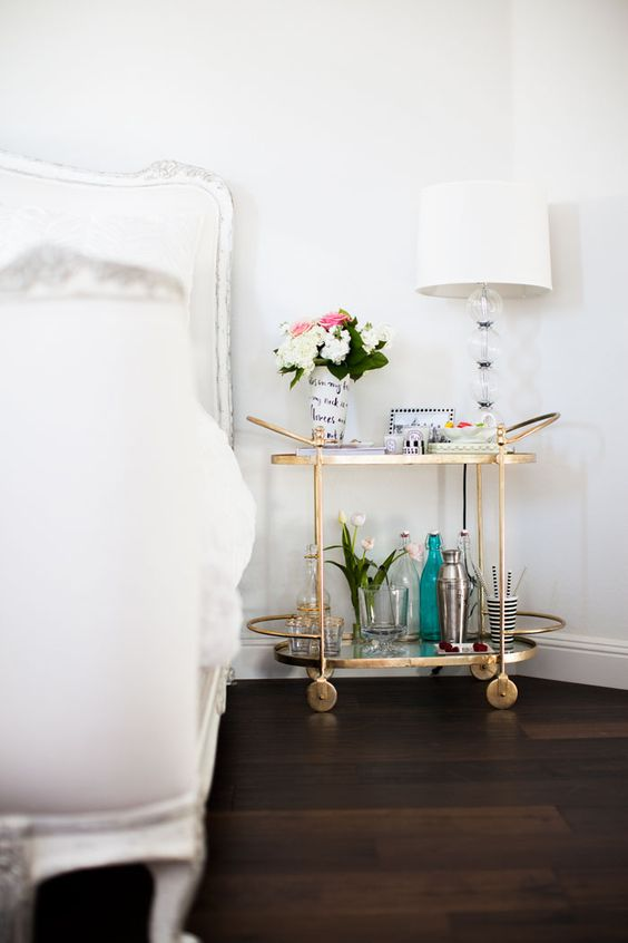 a bar cart as a nightstand with gilded accents is a very functional piece