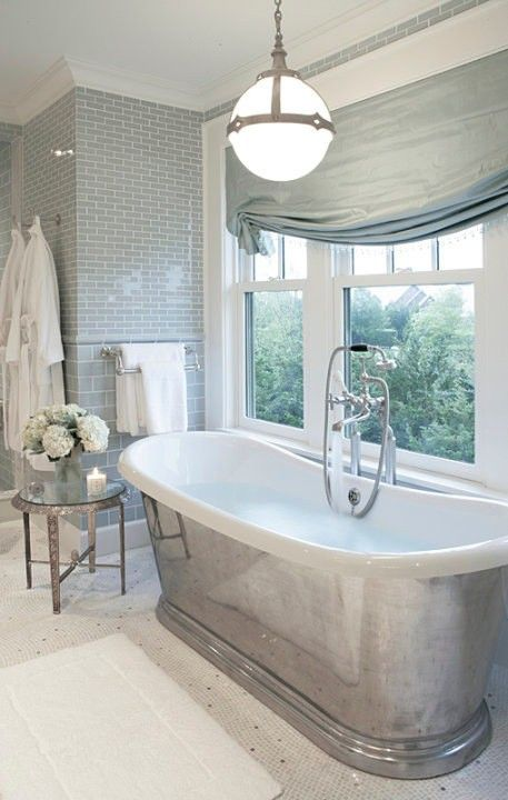 vintage-inspired bathroom with a metal-clad bathtub next to the window