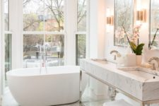 19 a comfy tub next to the window for a cool look, marble tiles