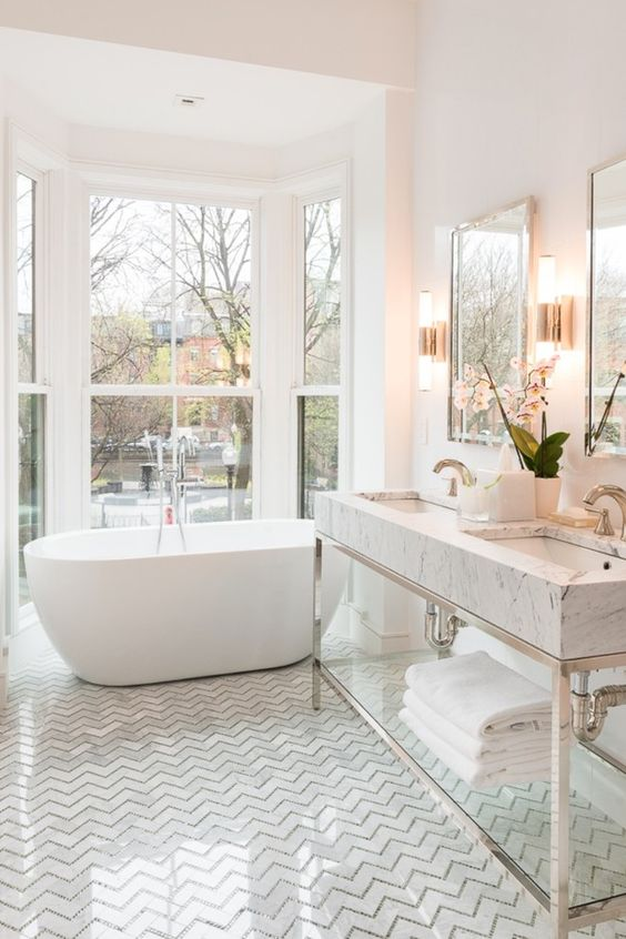 a comfy tub next to the window for a cool look, marble tiles
