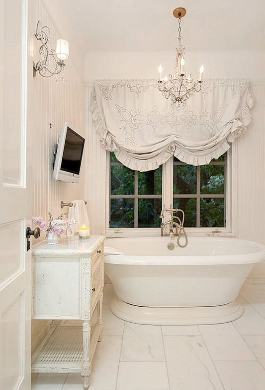 a modern bathtub on a stand in a shabby chic bathroom