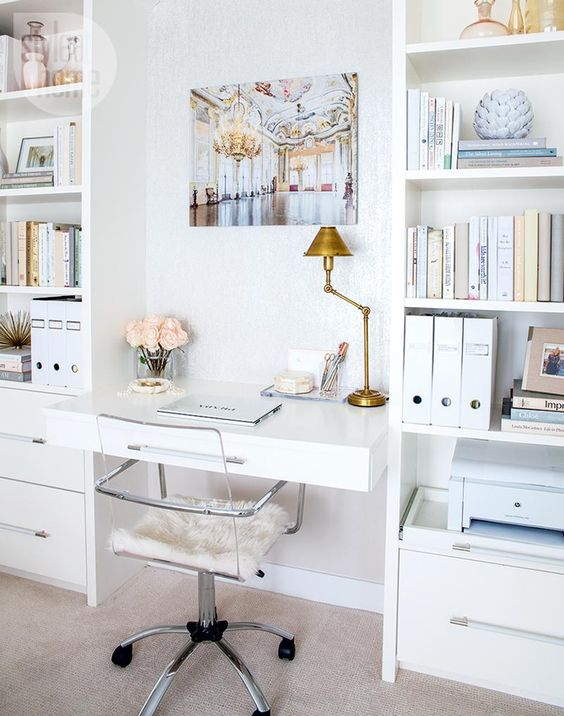a small desk stuck between two bookcases with drawers