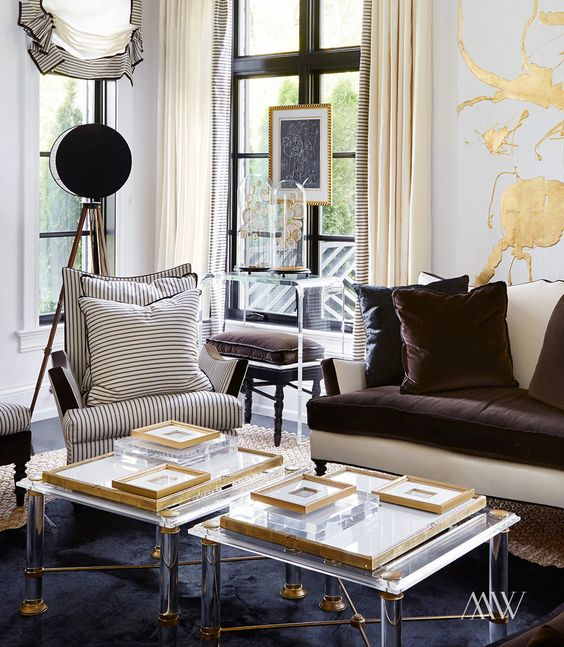 duo of lucite coffee tables with brass details make the living room exquisite