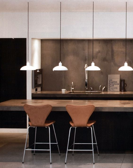 warm-colored concrete kitchen island and ocher leather chairs