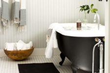 20 a black clawfoot bathtub with black legs makes this bathroom chic