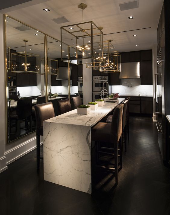 a marble waterfall kitchen island with upholstered chairs