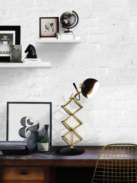 a retro lamp in brass and black with a rounded lampshade and a brass leg