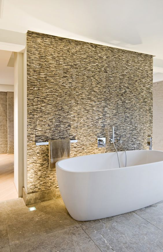 a stone accent wall and a white tub in front of it that stands out