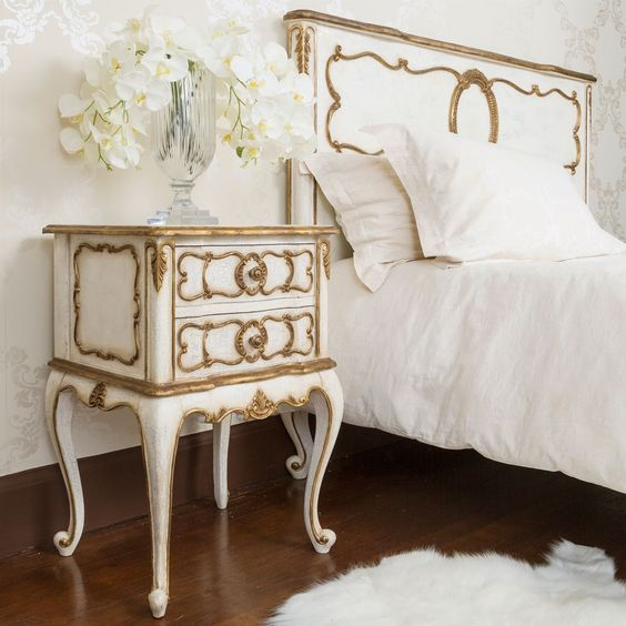 a white bedside table with gilded accents for an exquisite bedroom
