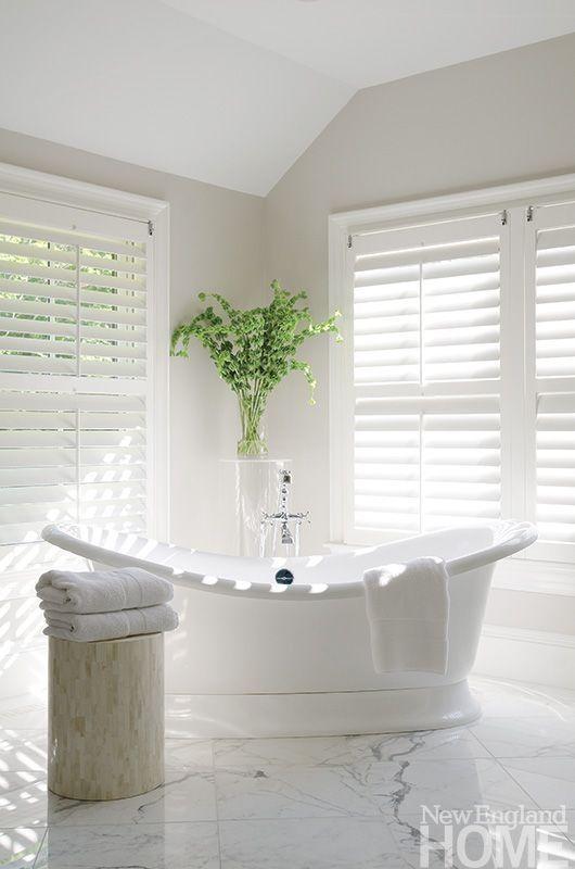 neutral feminine bathroom with a sculptural romantic tub