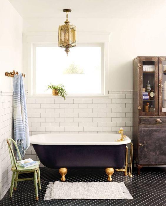 a black clawfoot tub and gold accents give the space an exquisite feel