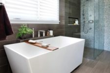 21 a home spa with a geometric bathtub next to the grey tile wall