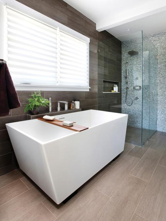 a home spa with a geometric bathtub next to the grey tile wall