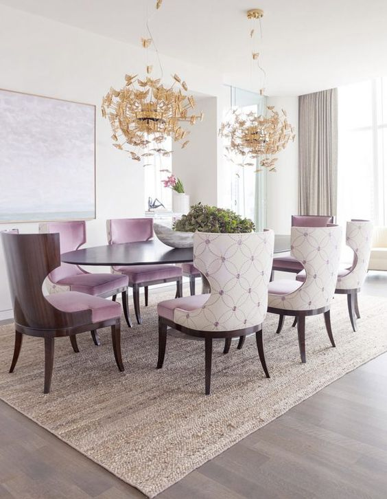 upholstered lavender chairs and gold butterfly chandeliers make the space girlish