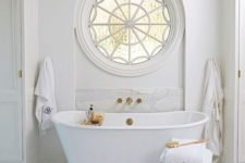 22 a luxury bathroom with a cool rounded window and a freestanding tub with gold accents