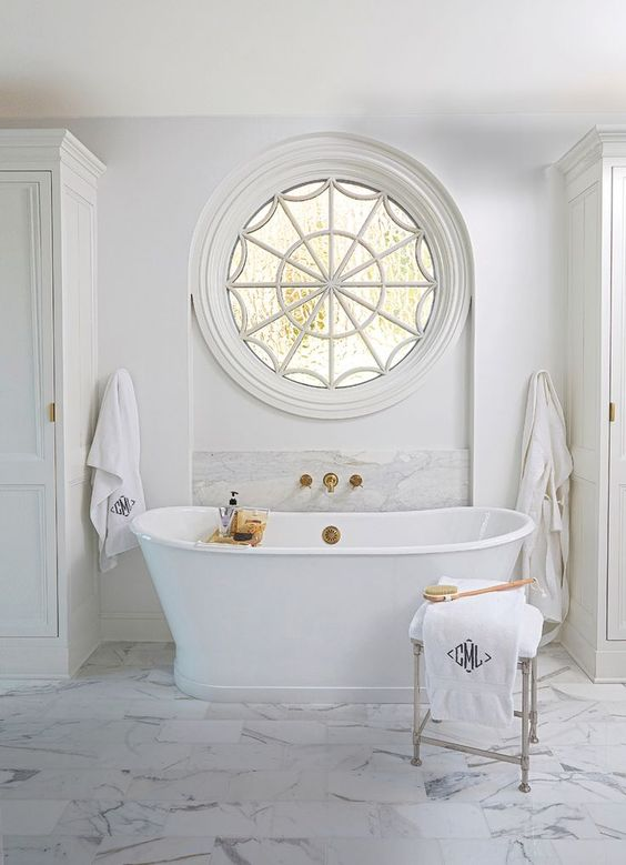 a luxury bathroom with a cool rounded window and a freestanding tub with gold accents