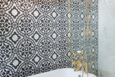 22 elegant retro bathroom with a black tub on black legs, brass details