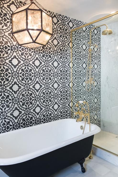 elegant retro bathroom with a black tub on black legs, brass details