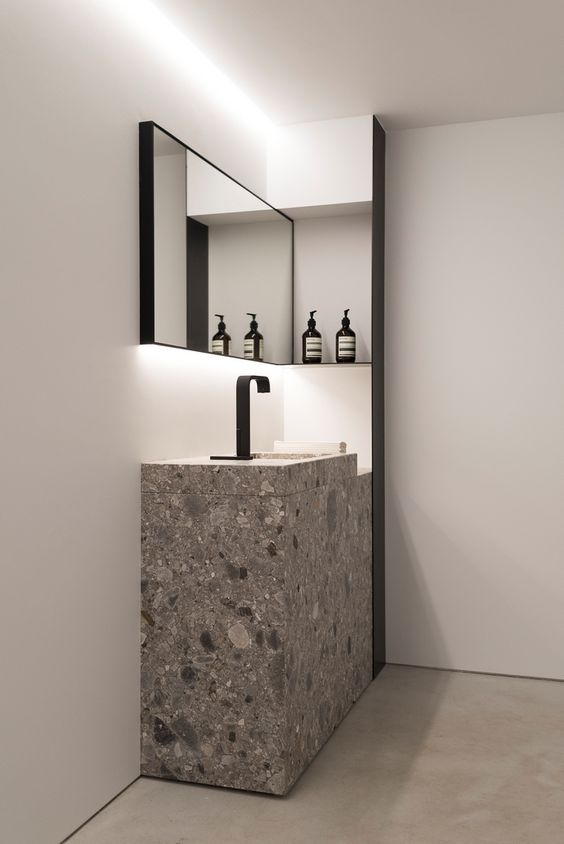grey stone square sink with a black faucet for a moody bathroom