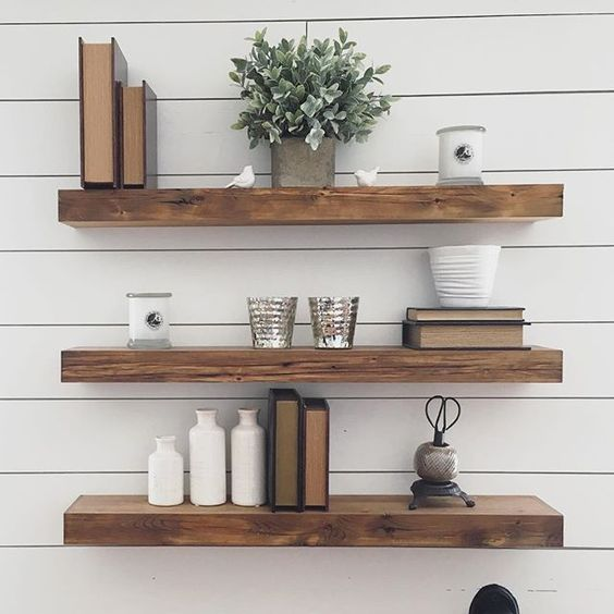 thick reclaimed wood floating shelves in front of a white plank wall