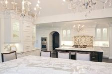 22 two chic chandleiers with some hanging crystals, marble and lots of white makes the kitchen exquisite